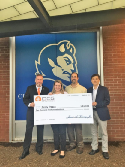 Emily Trezza accepts a $2,500 check from the Diversity Construction Group (DCG). From left to right: DCG President James A Keaney, Emily Trezza, Trezza's father Michael Trezza and CCSU Construction Management Professor Dr. Namhum Lee.