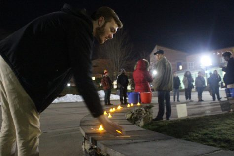 Freshman Adam Gwara puts a candle down at Nov. 20