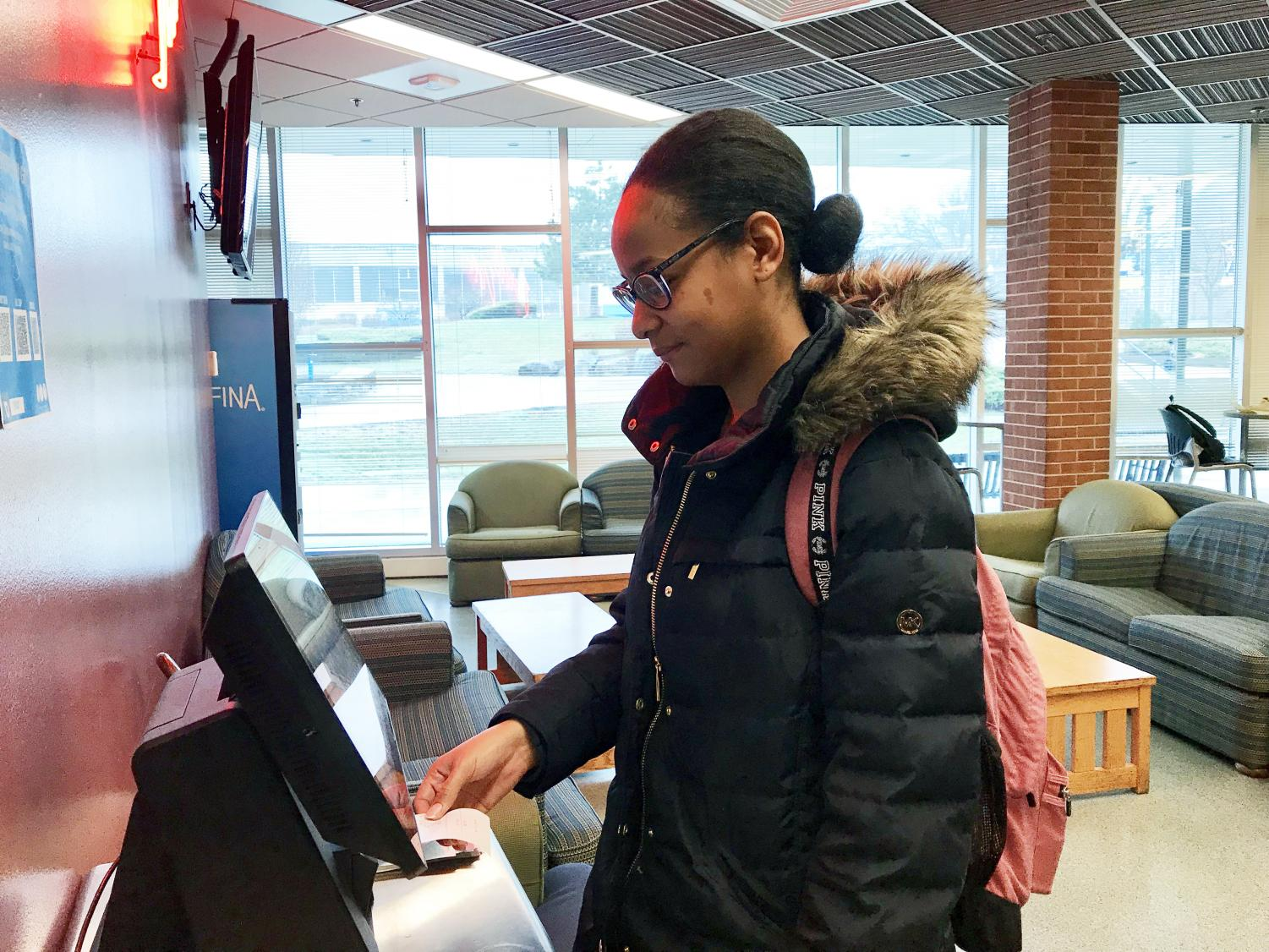 Junior criminology major Milagros Valdez orders food at Devil's Den on the touch screen system, which the SGA will try to make more accessible.