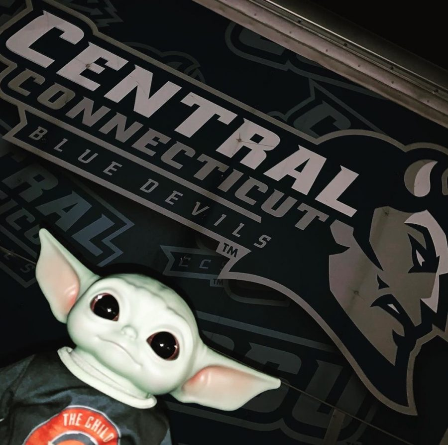Baby Yoda poses in front of the CCSU logo.